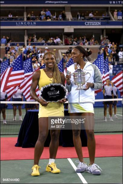 Serena Williams smilling as she reacts to big sister Venus's comments as they pose with their 2001 US Open Singles Trophies against a background of...