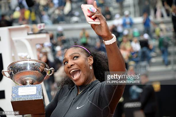 Serena Williams takes a selfie with the trophy after winning the final match of the WTA Tennis Open tournament game against US Madison Keys at the...