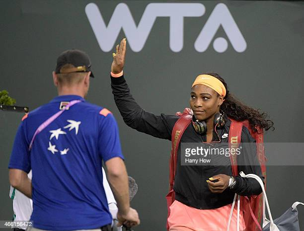 Serena Williams waves to the crowd as she enters stadium court before her match against Monica Niculescu of Romania during the BNP Parisbas Open at...