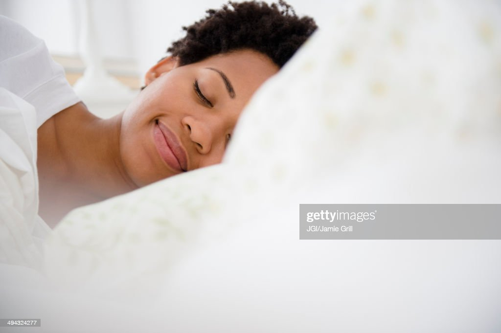 Serene Black woman laying in bed : Stock Photo