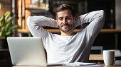 Serene businessman sitting at table feels satisfied accomplishing work
