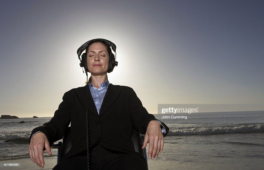 Serene Businesswoman Wearing Headphones Sits in a Chair by the Sea : Stock Photo