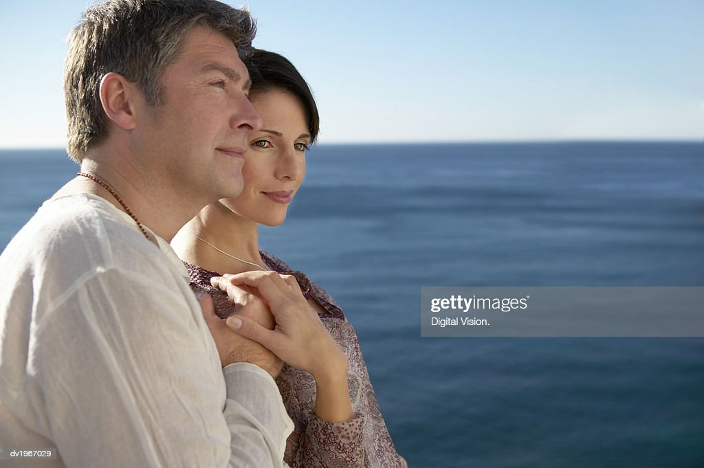 Serene Couple Stand by the Sea, Holding Hands : Stock Photo