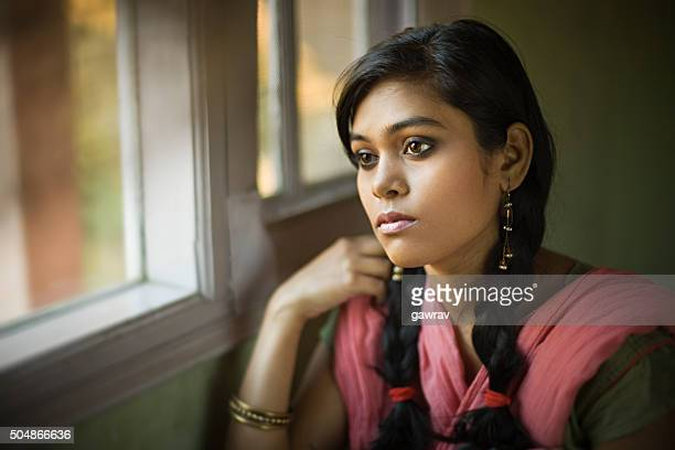 Serene girl looking away with blank expression sitting near window.