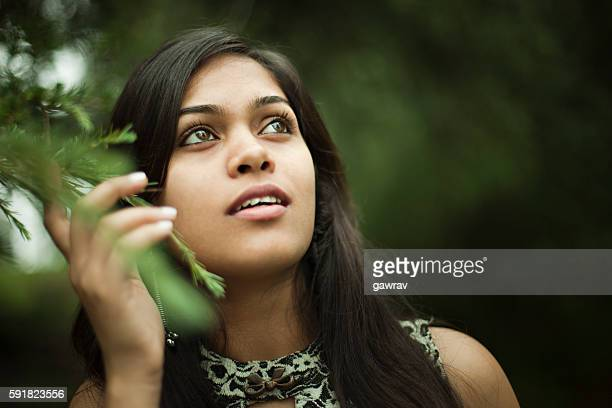 serene, happy girl looking up in nature holding tree branch. - black hair stock pictures, royalty-free photos & images