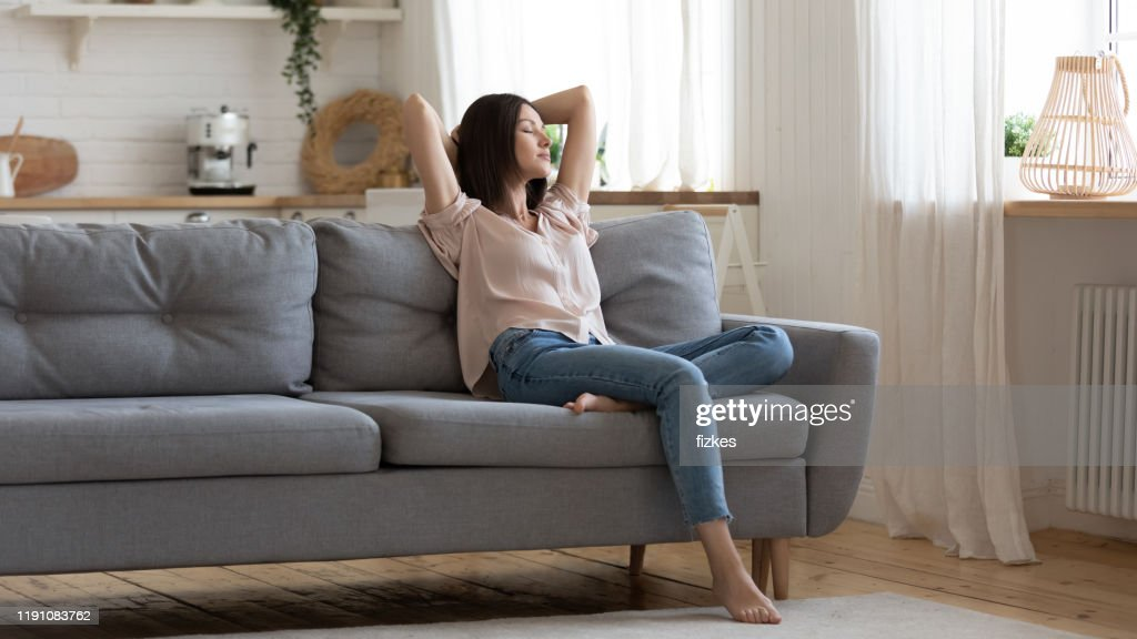 Serene lady lounge on sofa feel fatigue napping at home : Stock Photo