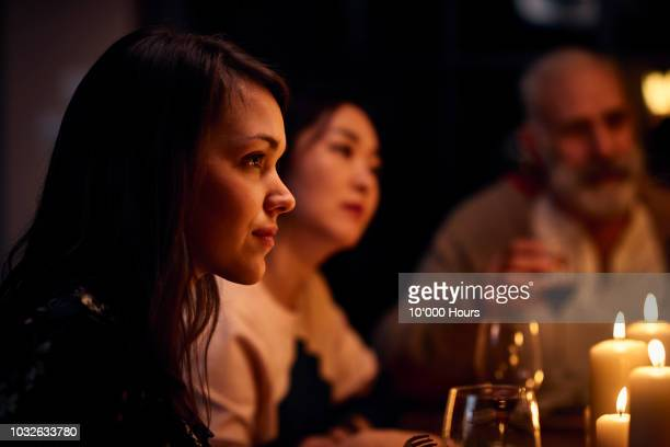 Serene looking woman at dinner party listening attentively