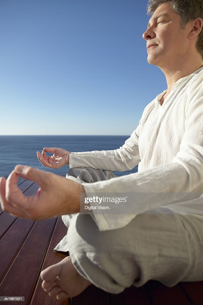 Serene Man Meditating in the Lotus Position by the Sea : Stock Photo