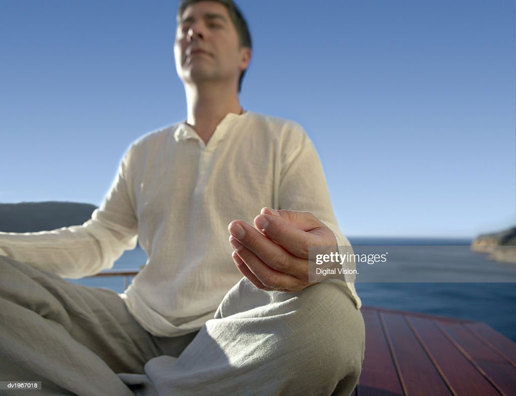 Serene Man Meditating Outdoors in the Lotus Position : Stock Photo