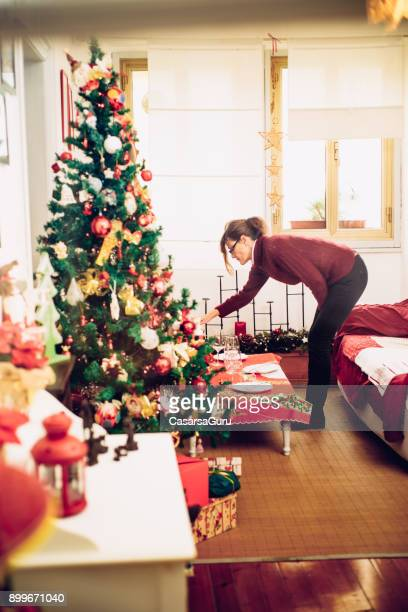 serene mature woman preparing the living room for christmas celebration - older woman bending over stock pictures, royalty-free photos & images