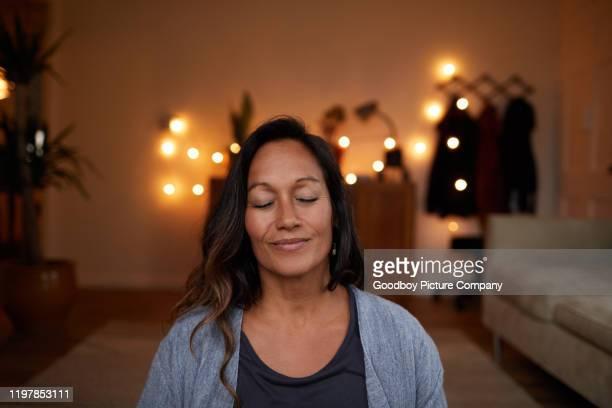 serene rijpe vrouw glimlachend tijdens het mediteren thuis - mindfulness stockfoto's en -beelden