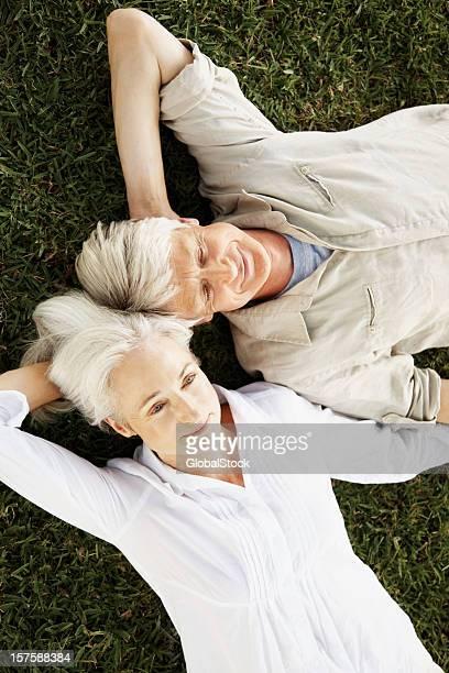 横になって静かな年配のカップルの芝生