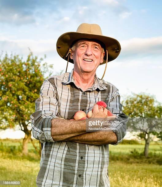 Serene senior farmer holding apples in orchard