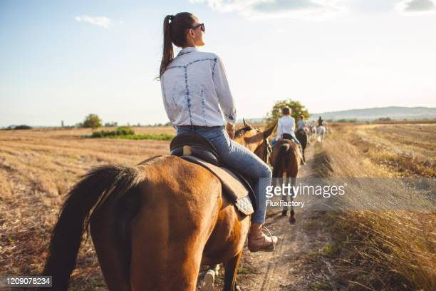 serene tourist woman riding a horse with a tourist group - horseback riding stock pictures, royalty-free photos & images