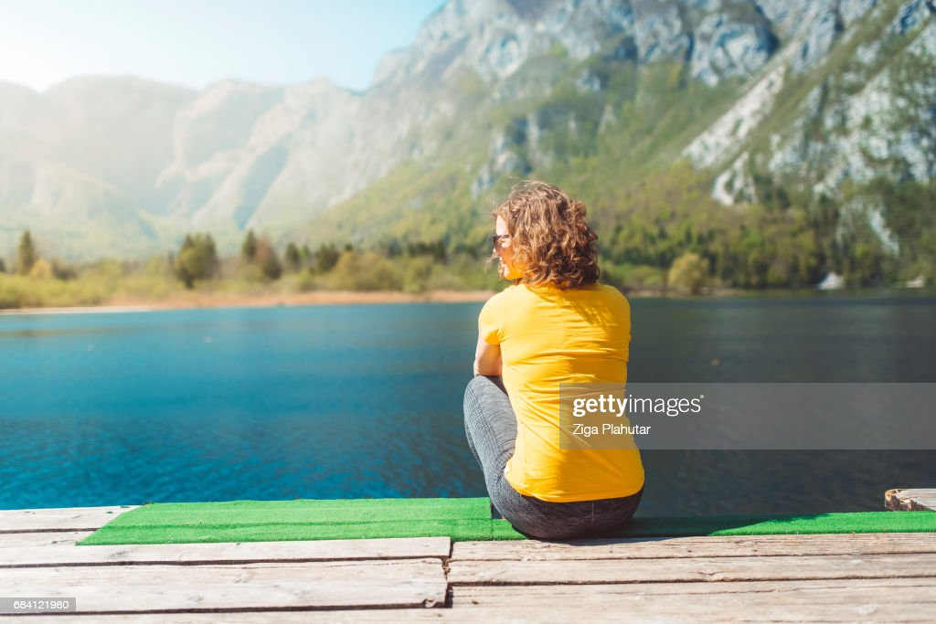 Serene woman by the lake : Stock Photo