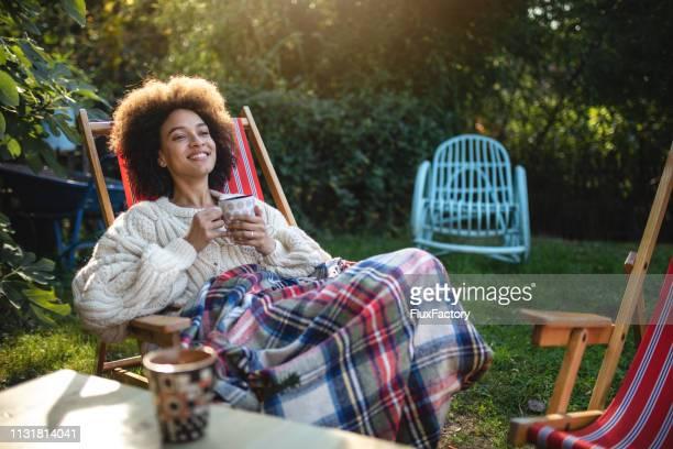 femme serein appréciant une journée ensoleillée à l'extérieur - chaise longue photos et images de collection