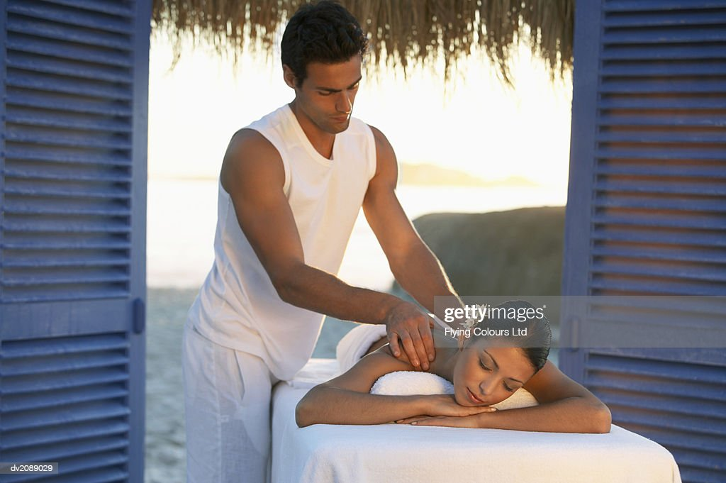 Serene Woman Lies on a Bed Being Given a Shoulder Massage by a Male Physical Therapist : Stock Photo