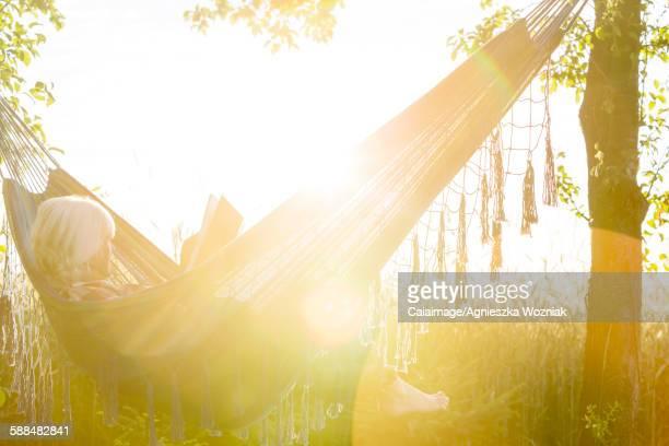 Serene woman reading book in sunny hammock