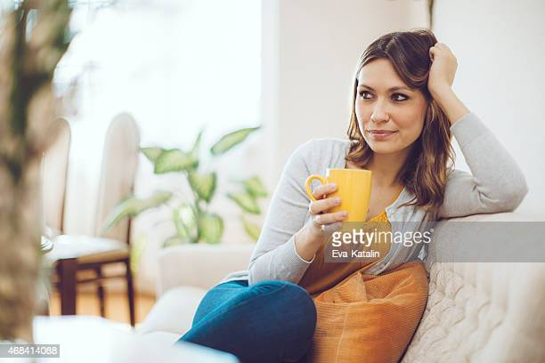Serene woman relaxing at home and drinking coffee