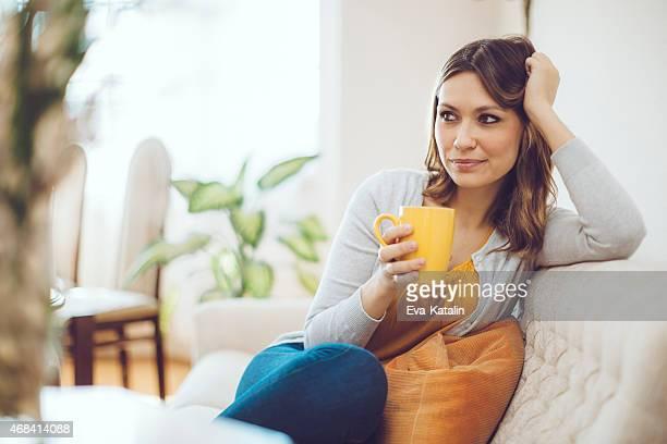 Mujer tranquila y relajante en casa bebiendo café