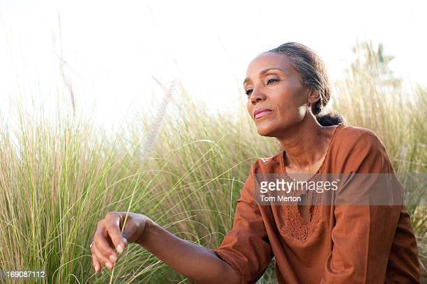 Serene woman sitting in sunny field