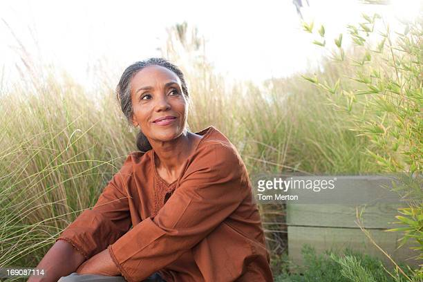 serene woman sitting in sunny field - mature women stock pictures, royalty-free photos & images