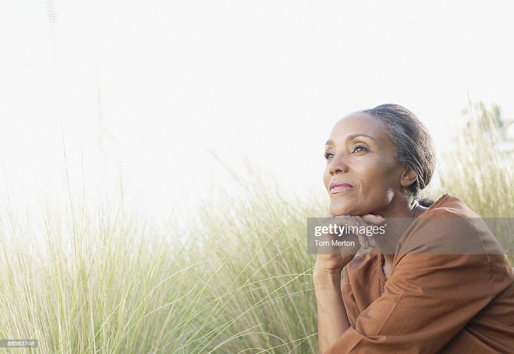 Serene woman sitting in sunny field : Stock Photo