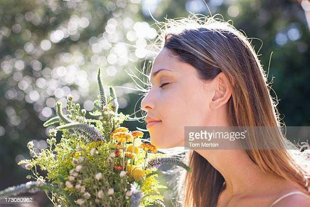 Serene woman smelling bouquet