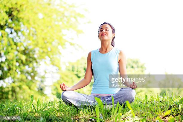 Serene young woman sitting in position lotus and doing yoga.