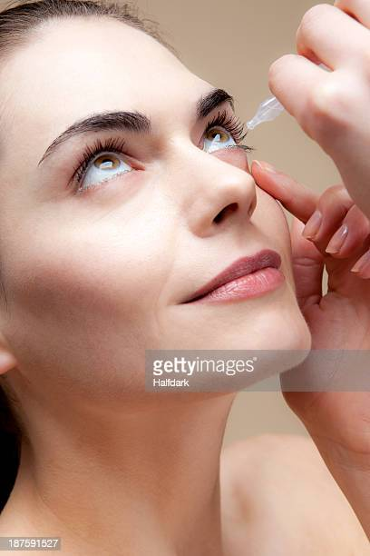 A serenely smiling young woman applying eye drops to her eyes