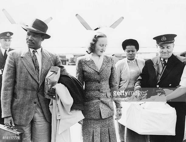 Seretse Khama, 29-year-old exiled chief designate of the Bamangwato tribe, with his ex-London wife Ruth walk from the giant flying boat that brought...