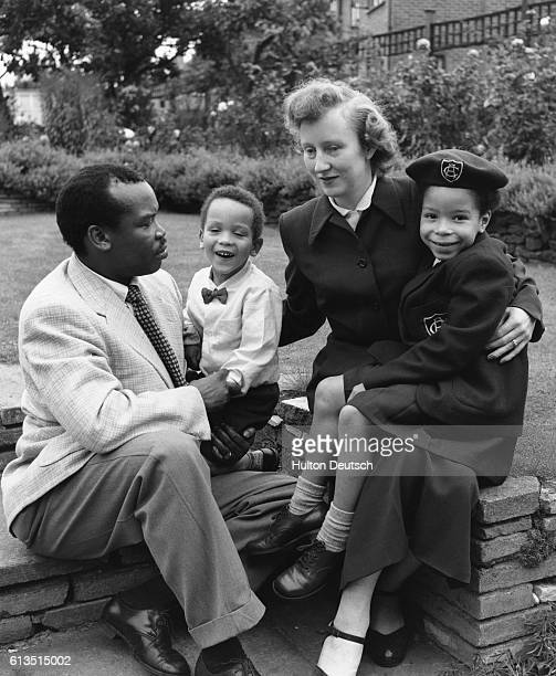 Seretse Khama, later the first President of Botswana when it gained independence, with his wife Ruth, and children in the garden of their Croydon...