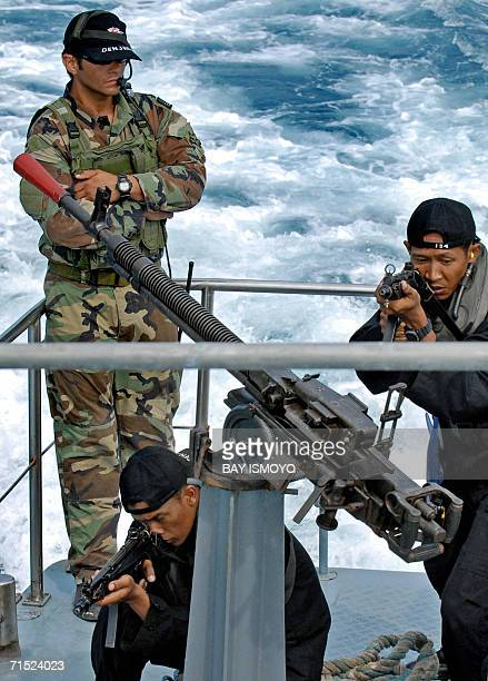 Sergant Chris stands by Indonesian marines antiterror troops aiming their weapons during the simulation of the interception of a pirate ship as part...