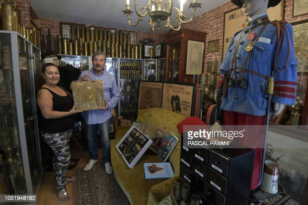 Serge and Chantal Giudice pose with a plate of a shell made by an African gunner for an exhibition in 1919 in the living room of their house in Balma...