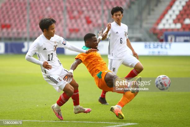 Serge Aurier of Ivory Coast is challenged by Takefusa Kubo of Japan during the international friendly match between Japan and Ivory Coast at Stadion...