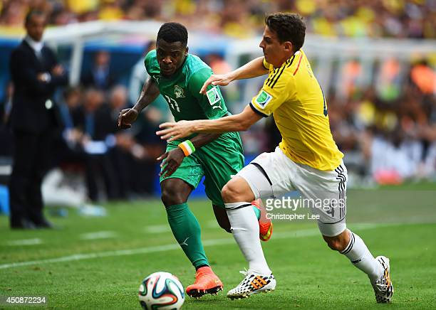 Serge Aurier of the Ivory Coast and Santiago Arias of Colombia compete for the ball during the 2014 FIFA World Cup Brazil Group C match between...