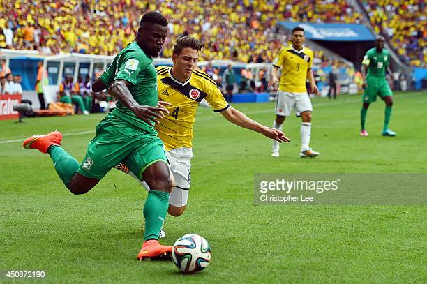 Serge Aurier of the Ivory Coast dribbles past Santiago Arias of Colombia during the 2014 FIFA World Cup Brazil Group C match between Colombia and...