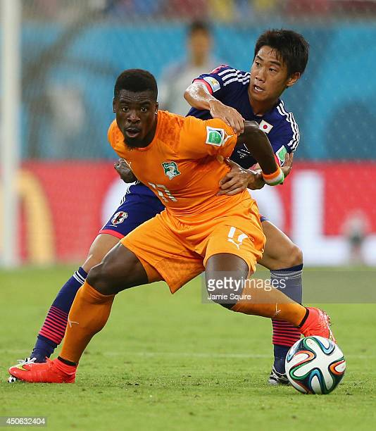 Serge Aurier of the Ivory Coast holds off a challenge by Shinji Kagawa of Japan during the 2014 FIFA World Cup Brazil Group C match between the Ivory...