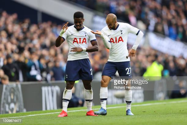 Serge Aurier of Tottenham Hotspur celebrates after scoring his team's second goal with teammate Lucas Moura during the Premier League match between...