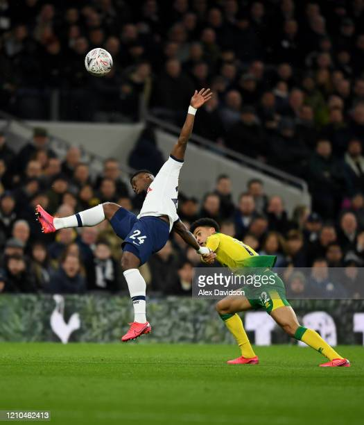 Serge Aurier of Tottenham Hotspur wins a header with pressure from Jamal Lewis of Norwich City during the FA Cup Fifth Round match between Tottenham...