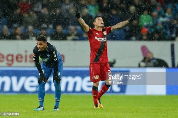Serge David Gnabry of Hoffenheim looks dejected and Charles Aranguiz of Leverkusen celebrates after winning the Bundesliga match between TSG 1899...
