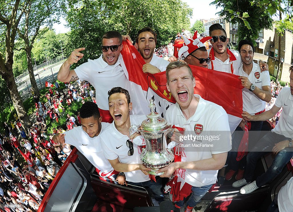 Serge Gnabry, Mesut Ozil, Lukas Podolski, Mathieu Flamini, Per Mertesacker, Kieran Gibbs, Olivier Giroud and Mikel Arteta pose at the Arsenal Victory Parade after winning the FA Cup Final on May 18, 2014 in London, England.