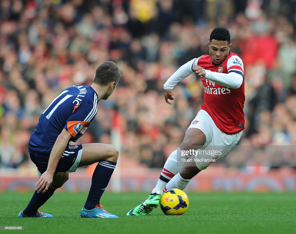 Serge Gnabry of Arsenal breaks past Alexander Kacaniklic of Fulham during the match at Emirates Stadium on January 18, 2014 in London, England.