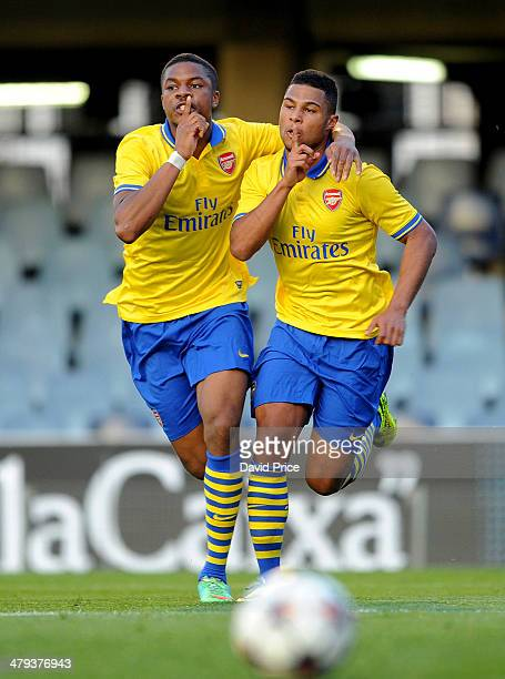 Serge Gnabry of Arsenal celebrates scoring a goal with teammate Chuba Akpom during the UEFA Youth League Quarter Final match between Barcelona U19...