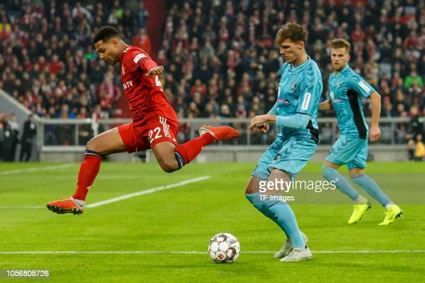 Serge Gnabry of Bayern Muenchen and Manuel Gulde of SportClub Freiburg battle for the ball during the Bundesliga match between FC Bayern Muenchen and...