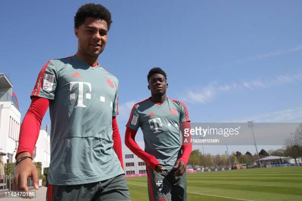 Serge Gnabry of Bayern Muenchen arrives with his team mate Alphonso Davies for a FC Bayern Muenchen training session at Saebener Strasse training...
