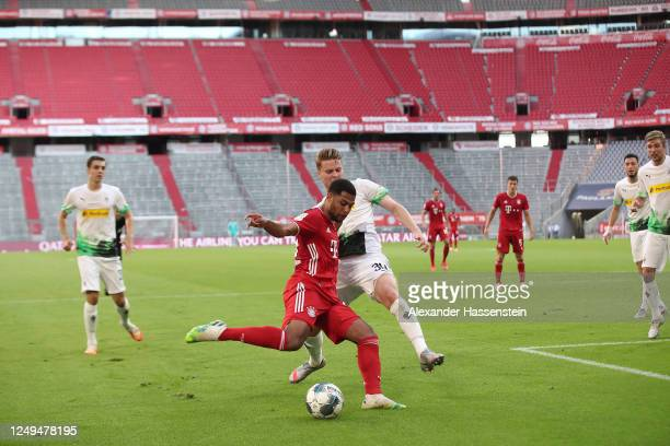 Serge Gnabry of Bayern Muenchen is challenged by Nico Elvedi of Borussia Monchengladbach during the Bundesliga match between FC Bayern Muenchen and...
