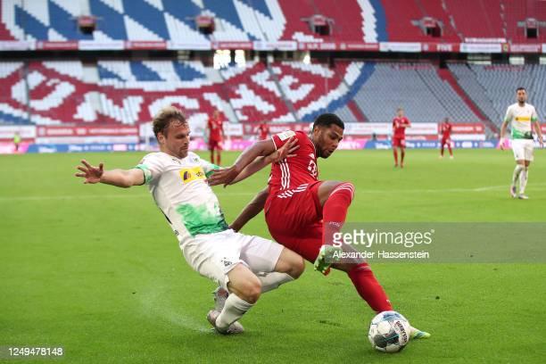 Serge Gnabry of Bayern Muenchen is challenged by Tony Jantschke of Borussia Monchengladbach during the Bundesliga match between FC Bayern Muenchen...