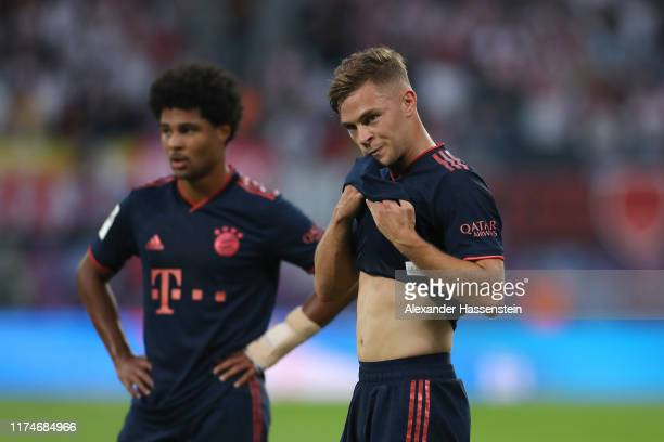 Serge Gnabry of Bayern Muenchen reacts with his team mate Joshua Kimmich during the Bundesliga match between RB Leipzig and FC Bayern Muenchen at Red...