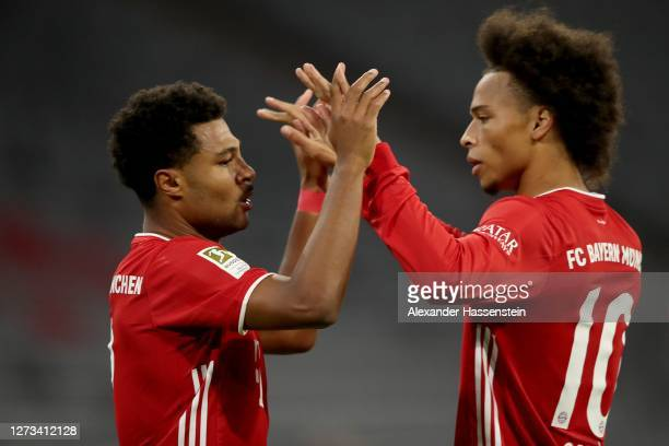 Serge Gnabry of Bayern Munich celebrates scoring the opening goal with his team mate Leroy Sane during the Bundesliga match between FC Bayern...